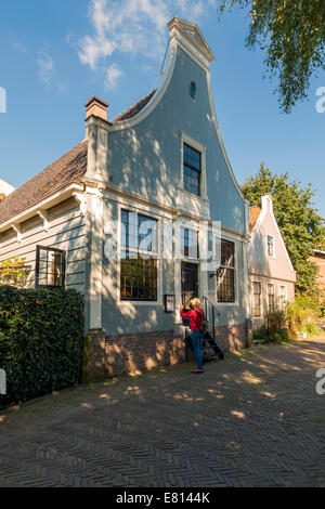 Woman taking a photo of a historic house in 'Broek in Waterland', North Holland, The Netherlands. - Stock Photo