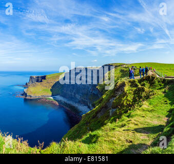 Tourists at the Cliffs of Moher, The Burren, County Clare, Republic of Ireland - Stock Photo