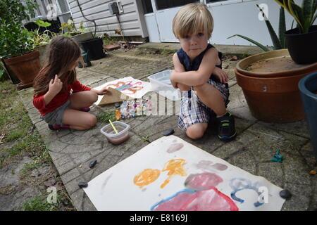 Boy and girl making art in backyard - Stock Photo