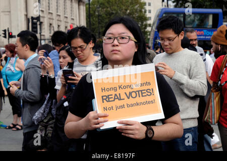 A young woman from Hong Kong holds a placard reading ' Hong Kong wants real votes' - Stock Photo