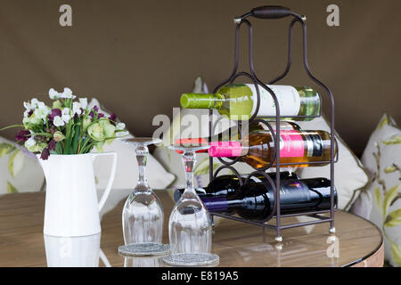 Rack of different wines and two wine glasses with jug of flowers on a dinning table - Stock Photo