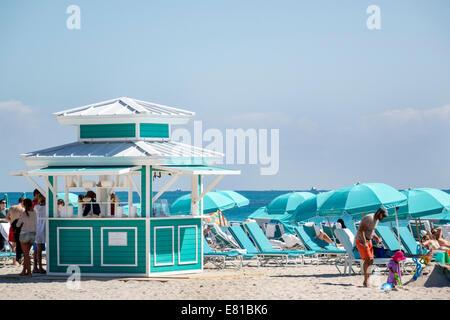 Miami Beach Florida kiosk rental umbrellas lounge chairs Atlantic Ocean - Stock Photo