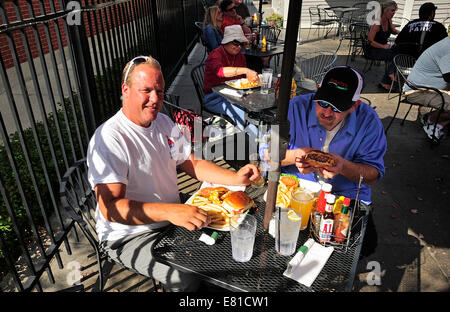 Two men eating hamburgers at outdoor cafe. - Stock Photo