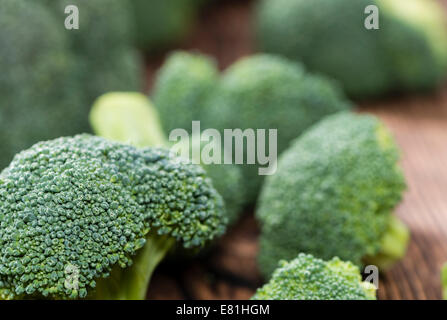 Portion of Raw Broccoli on dark wooden background - Stock Photo