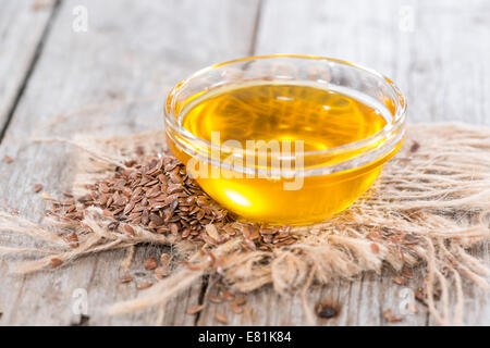 Portion of golden Linseed Oil with some seeds around - Stock Photo