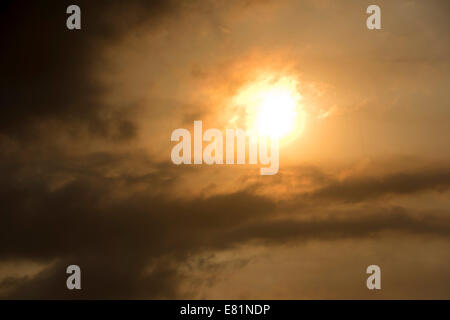 Sun behind clouds and brownish ash and gas clouds of the Holuhraun fissure eruption, north of the Bárðarbunga volcano - Stock Photo