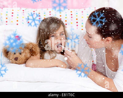 Composite image of mother taking her daughters temperature with a thermometer - Stock Photo
