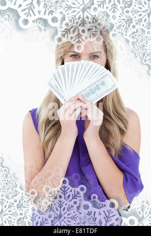 Composite image of blonde woman hiding her face behind a fan of notes - Stock Photo