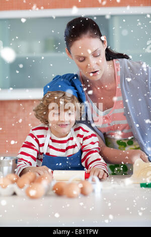 Composite image of beautiful mother and her son baking at home - Stock Photo