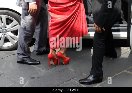 Woman wearing a red dress and red high heel shoes getting into a car  Taormina Sicily Italy - Stock Photo