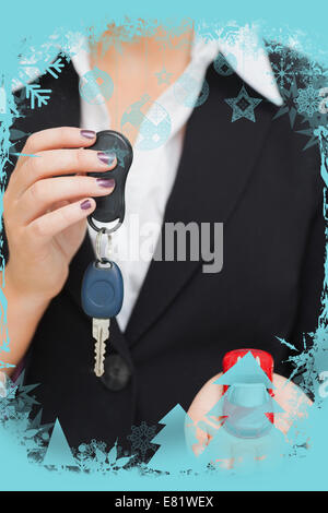 Composite image of woman holding key and small car in her palm - Stock Photo