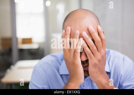 Businessman with head in hands at office - Stock Photo