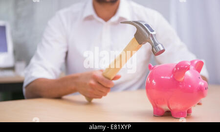 Man breaking piggy bank with hammer - Stock Photo