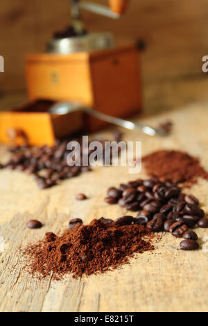 Fresh milled coffee beans with old vintage grinder - Stock Photo