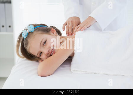 Small smiling girl lying on a table - Stock Photo