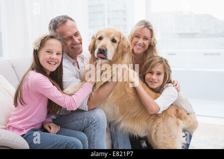 Cute family petting their golden retriever on the couch - Stock Photo