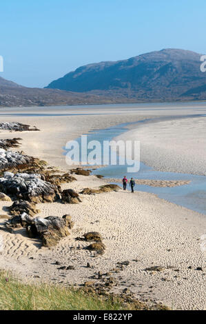 Couple walking on Luskentyre Beach on the west coast of the Isle of Harris. - Stock Photo