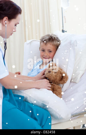 Female doctor listening to a child chest and a teddy bear - Stock Photo