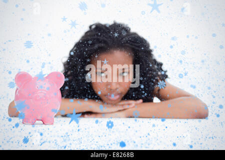 Young woman lying down resting her head on her hands is looking at a piggy bank - Stock Photo