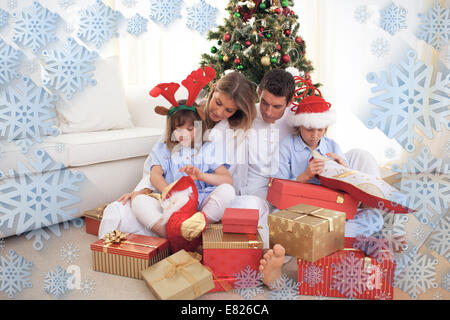 Composite image of portrait of a happy family opening christmas gifts - Stock Photo