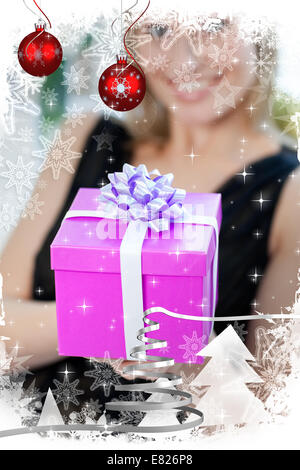 Blonde woman opening a gift sitting on a sofa - Stock Photo