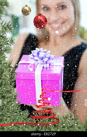 Blond woman opening a gift sitting on a sofa - Stock Photo