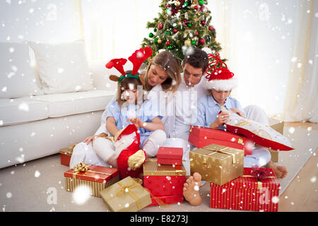 Portrait of a happy family opening christmas gifts - Stock Photo