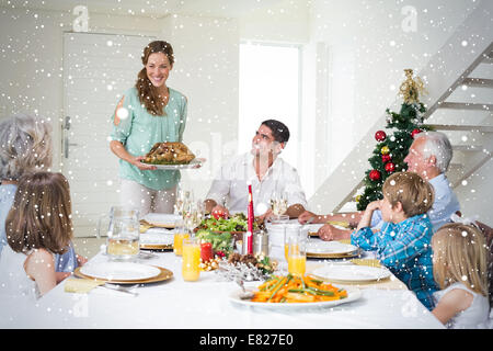 Composite image of mother serving christmas meal to family - Stock Photo