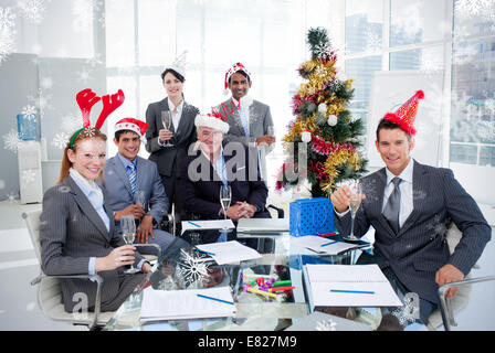 Portrait of a smiling business team wearing novelty christmas hat - Stock Photo