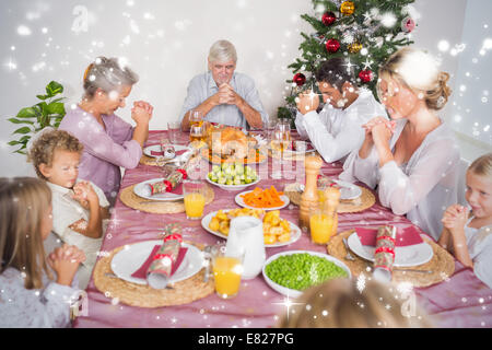 Composite image of family saying grace before christmas dinner - Stock Photo