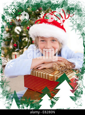 Composite image of happy little boy with christmas presents - Stock Photo