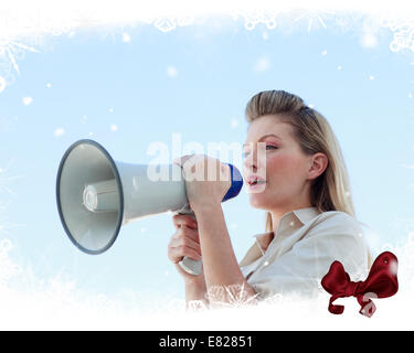 Blonde businesswoman shouting through megaphone - Stock Photo