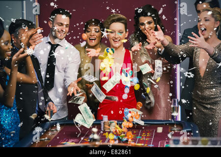 People throwing chips and cash on roulette table - Stock Photo
