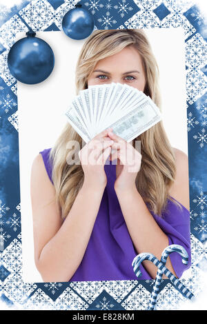 Blonde woman hiding her face behind a fan of notes - Stock Photo