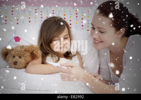 Composite image of mother taking her daughters temperature - Stock Photo