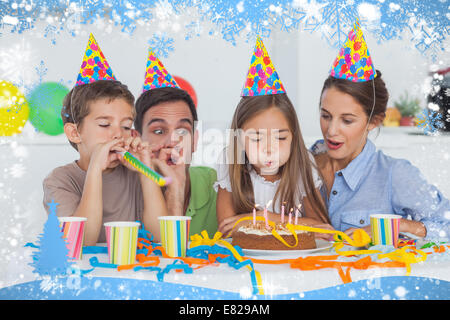 Little girl blowing her candles during her birthday party - Stock Photo