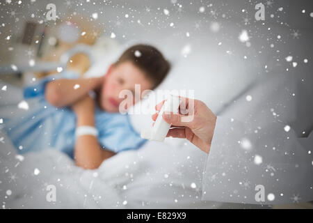 Doctor holding asthma inhaler with boy in hospital - Stock Photo
