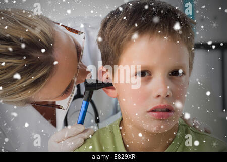 Composite image of boy being examined by doctor with otoscope - Stock Photo