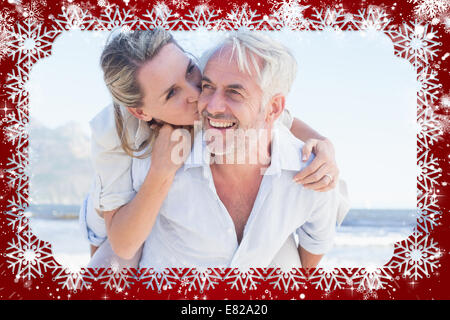 Man giving his smiling wife a piggy back at the beach - Stock Photo