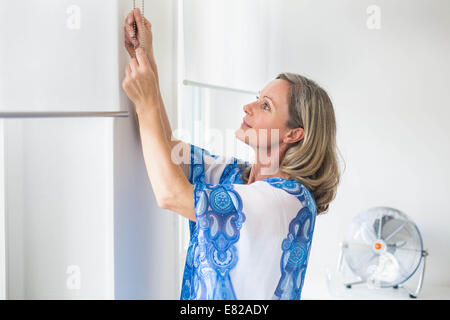 Adjusting blind. - Stock Photo