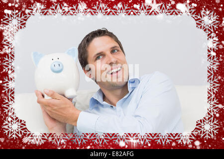 Handsome casual man with piggy bank in living room - Stock Photo