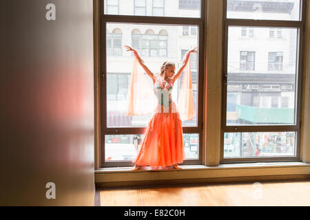 Dancer in dance studio. A woman posing at a window. - Stock Photo