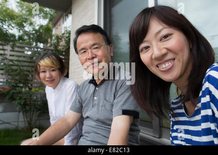 A man and two women sitting at home in a garden. A father and two daughters. - Stock Photo