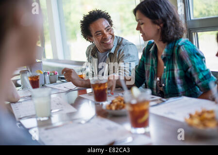 A group of friends eating at a diner. A couple seated side by side. - Stock Photo