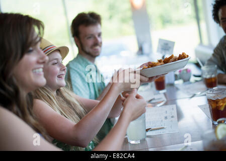 A group of friends eating at a diner. - Stock Photo