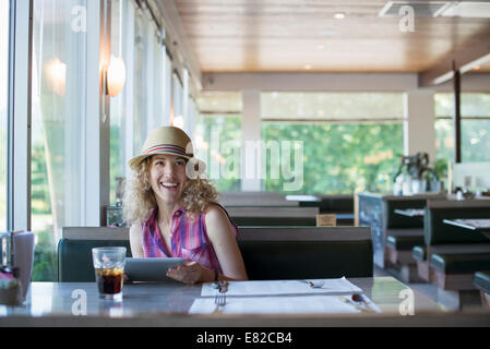 A woman in a hat sitting in a diner, holding a digital tablet. - Stock Photo