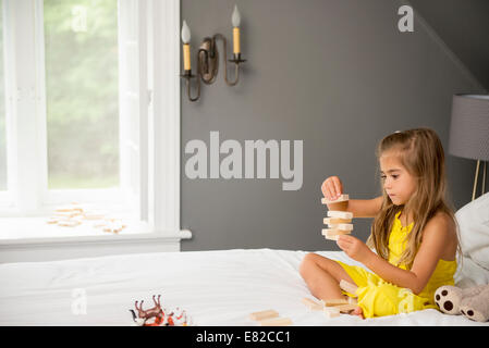 A girl sitting on a bed, playing with building blocks. - Stock Photo