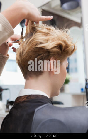 Smiling hairdresser cutting customers hair - Stock Photo