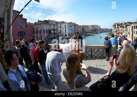 Newly married Asian couple having their wedding photos taken on the Rialto Bridge, Venice, Italy, with Canal Grande - Stock Photo