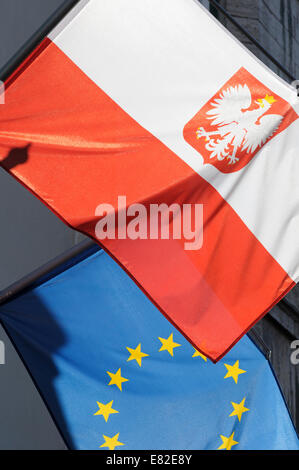 Estonia, Tallinn. The Polish and European Union flags overlap as they fly from flagpoles over a shop in Tallinn. - Stock Photo